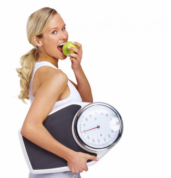Young woman eating apple and carrying a weight scale over white background