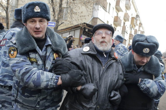 Police detain a protester outside a courthouse in Moscow