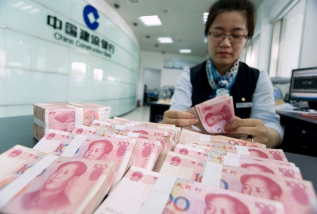 A clerk counts Chinese 100 yuan banknotes at a branch of China Construction Bank in Hai'an, Jiangsu province