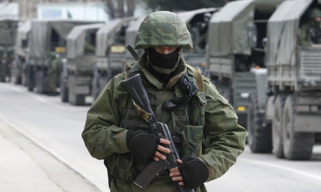 Russian soldiers wait outside a Ukrainian border guard post in the Crimean town of Balaclava