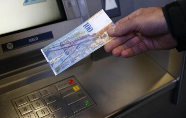 A man holds a 100 Swiss Francs bank note in front of an ATM in this illustration picture taken in Bern